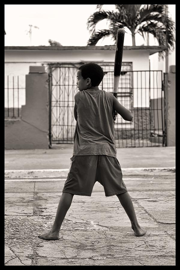 Boy playing baseball in the street (Cuba, 2014)
